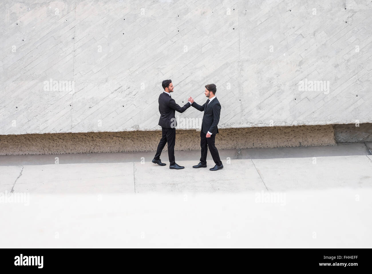 Two people standing opposite each other stock photos two people two businessmen wearing black suits greeting each other stock image m4hsunfo