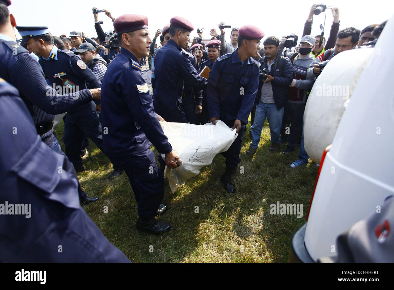 Pokhara. 25th Feb, 2016. Nepalese policemen and army personnel carry bodies of those who died in an aircraft crash - Stock Image