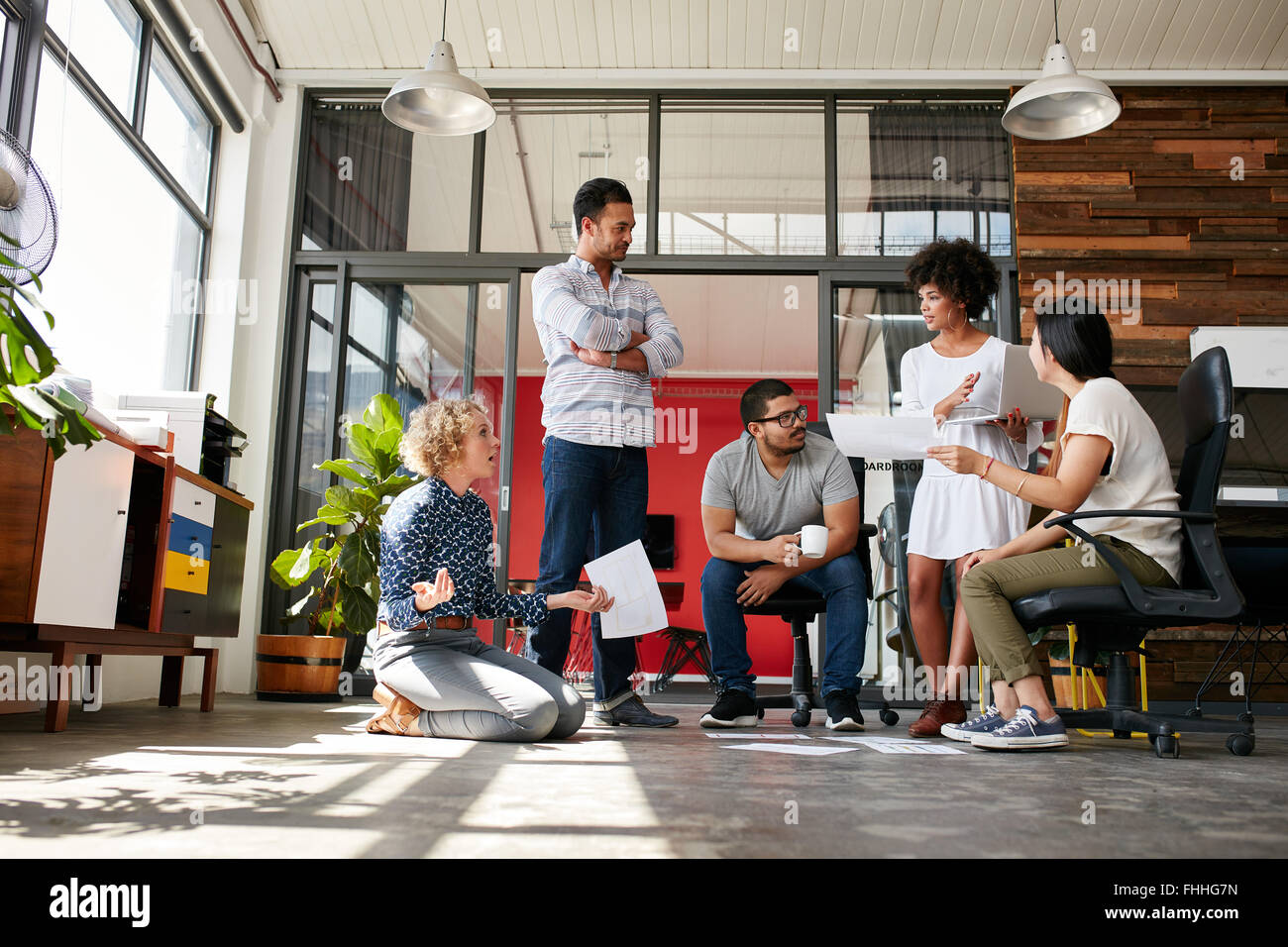 Creative team having a discussion on new design project in office. Project plan laid on floor with coworkers meeting - Stock Image