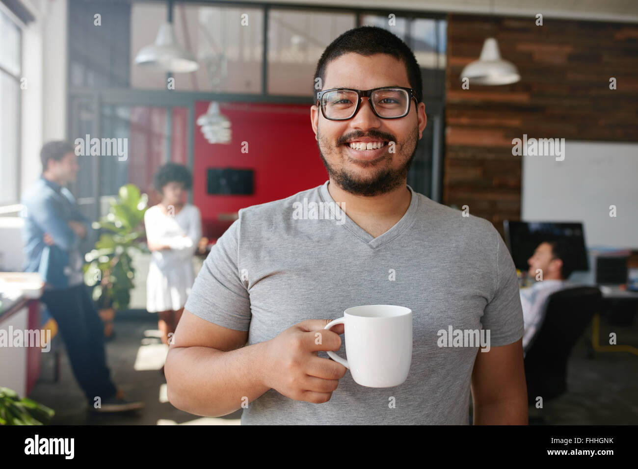 Portrait of smiling office worker having a coffee with his colleagues talking in the background. - Stock Image