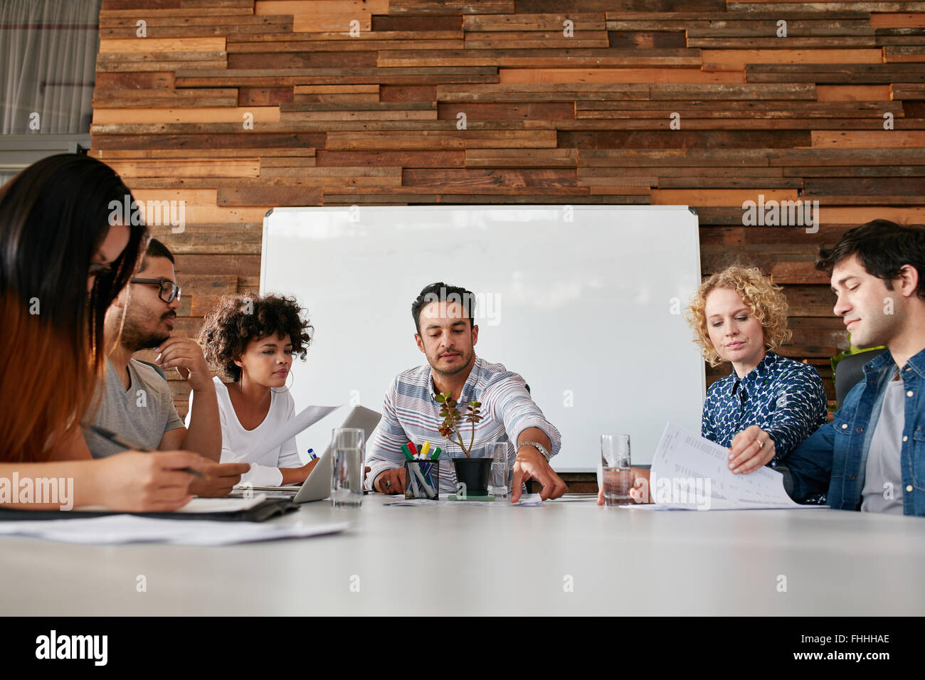 Portrait of team of young people having a meeting in office. Young men and women sitting around conference table - Stock Image