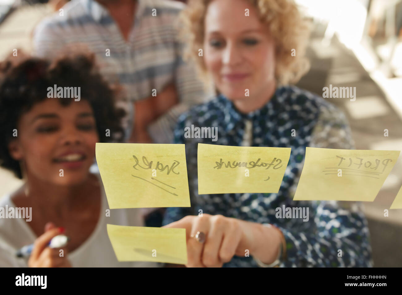 Young businesswoman showing her coworker an idea posted on a sticky note wall. Creative professionals brainstorming - Stock Image