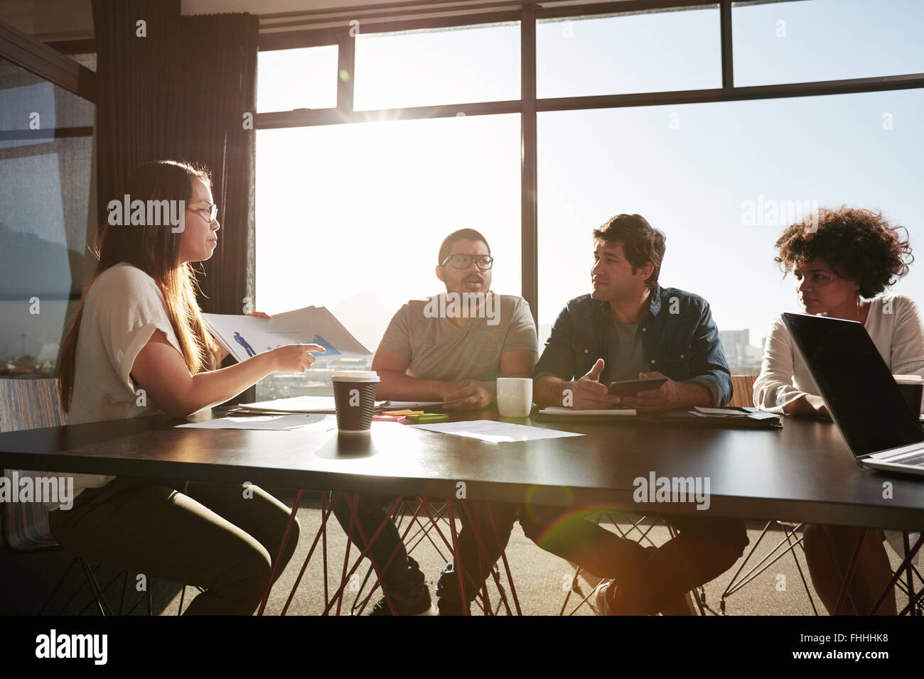 Young business woman consulting new business plans with her colleagues. Creative people discussing documents and - Stock Image