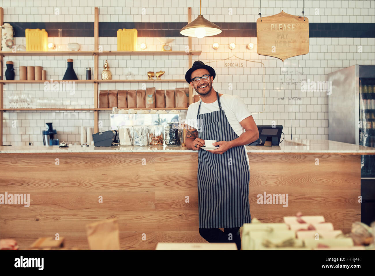 Portrait of happy young man wearing an apron and hat standing at a cafe counter holding a cup of coffee. Coffee - Stock Image