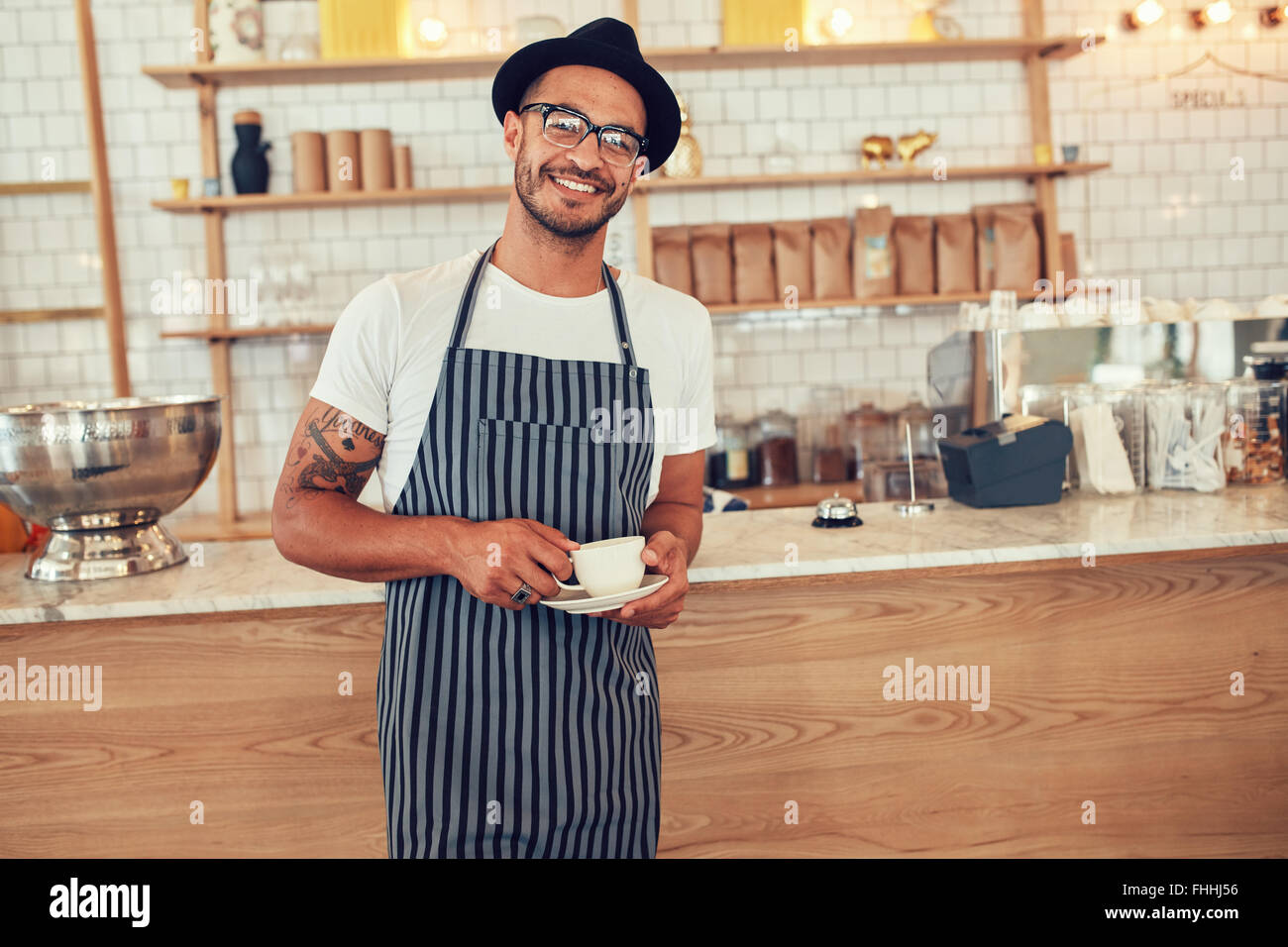 Portrait of happy young barista at work. Caucasian man wearing apron and hat standing in front of cafe counter with - Stock Image
