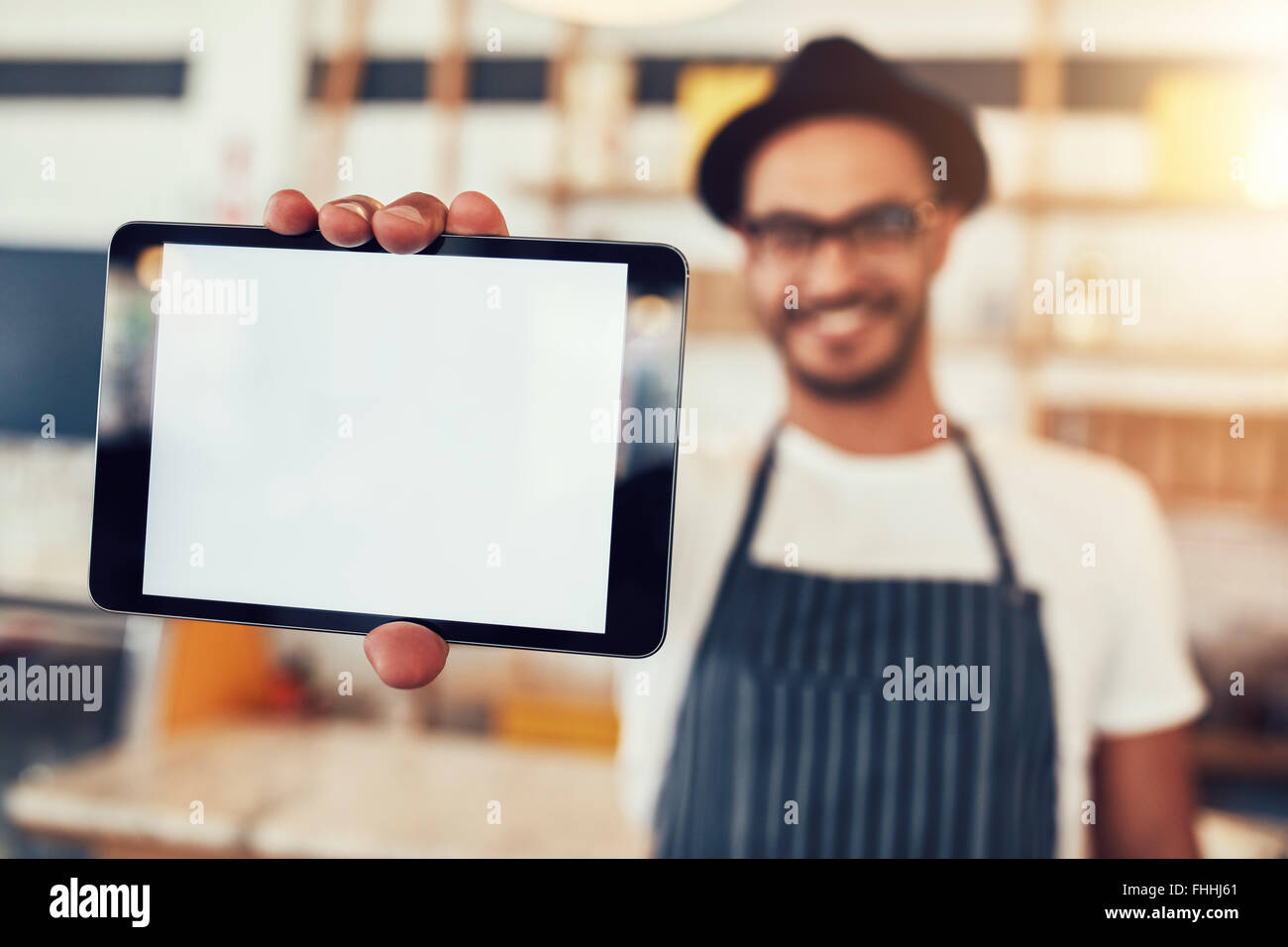Close up portrait of a man holding up a digital tablet with a blank display. Man working in cafe showing a touch - Stock Image