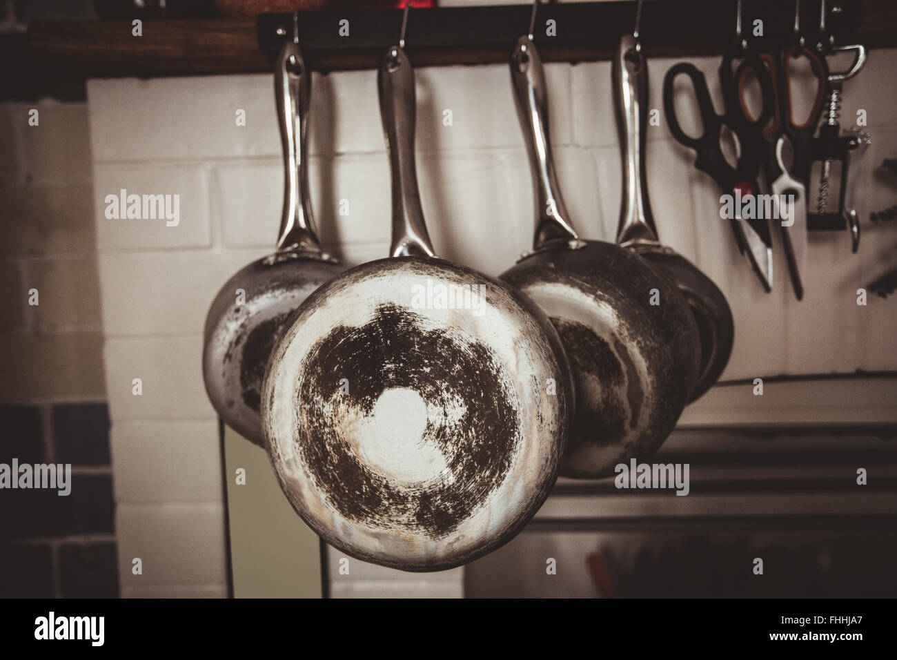 Pots and pans hooked in the kitchen - Stock Image