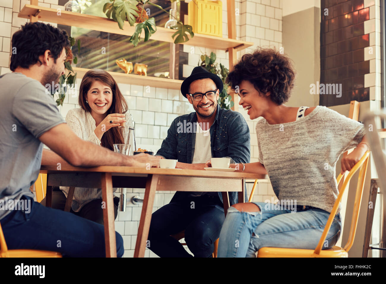 Portrait of cheerful young friends having fun while talking in a cafe. Group of young people meeting in a cafe. - Stock Image