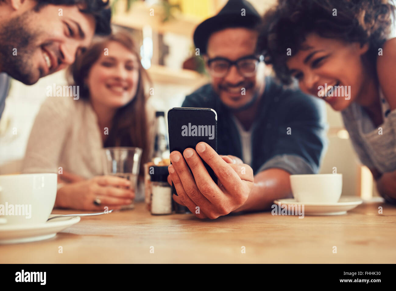 Group of friends having fun at the cafe and looking at smart phone. Man showing something to his friends sitting - Stock Image
