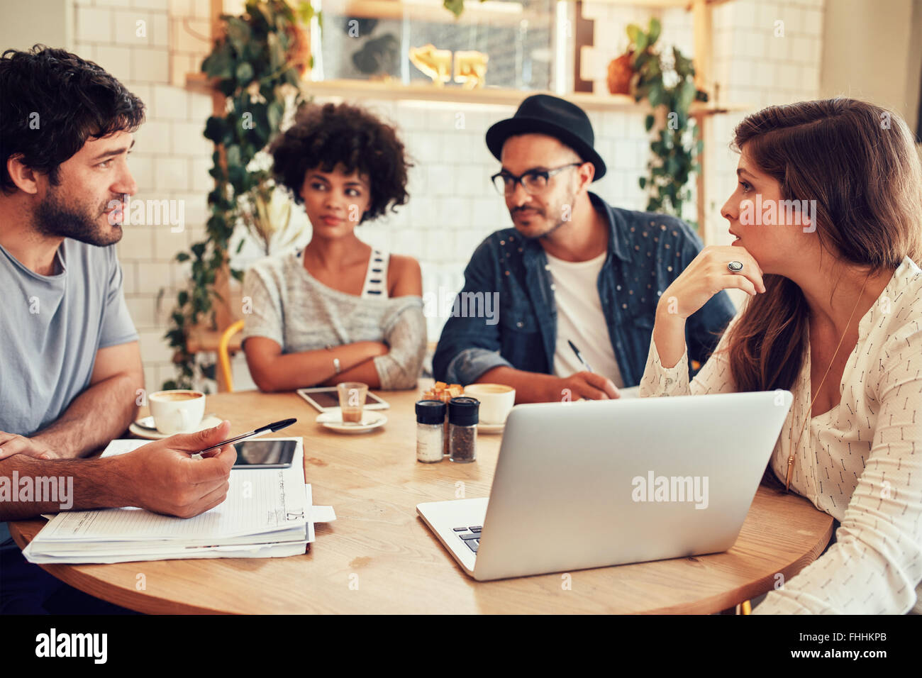 Portrait of young people sitting around in cafe with a laptop. Creative team meeting in a coffee shop for discussing - Stock Image