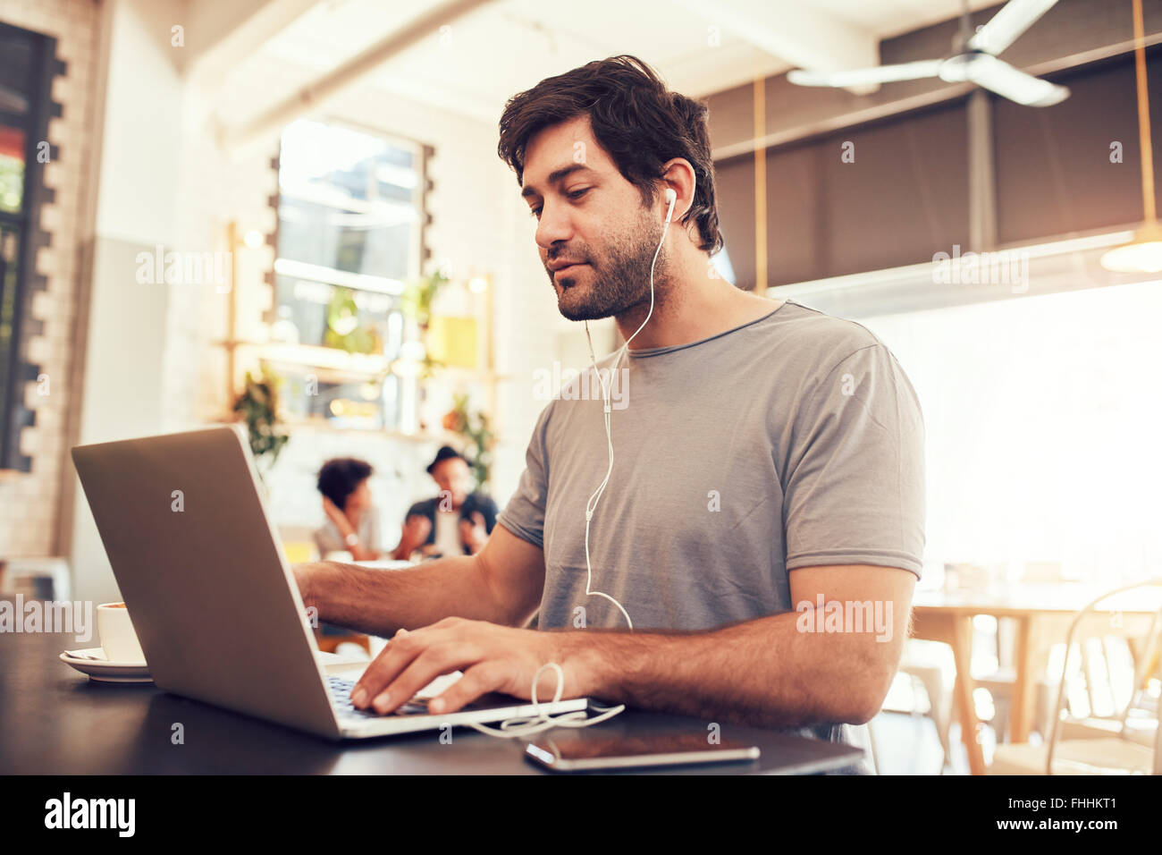 Portrait of a young caucasian man with earphones using laptop at a cafe. Man with beard working on laptop computer - Stock Image
