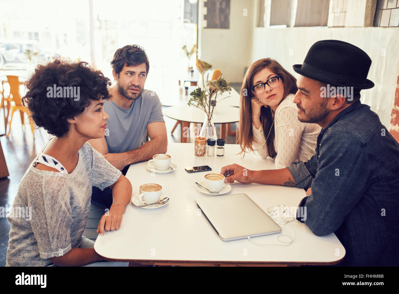 Portrait of young men and women sitting at a cafe table and talking. Group of young friends meeting at a coffee - Stock Image