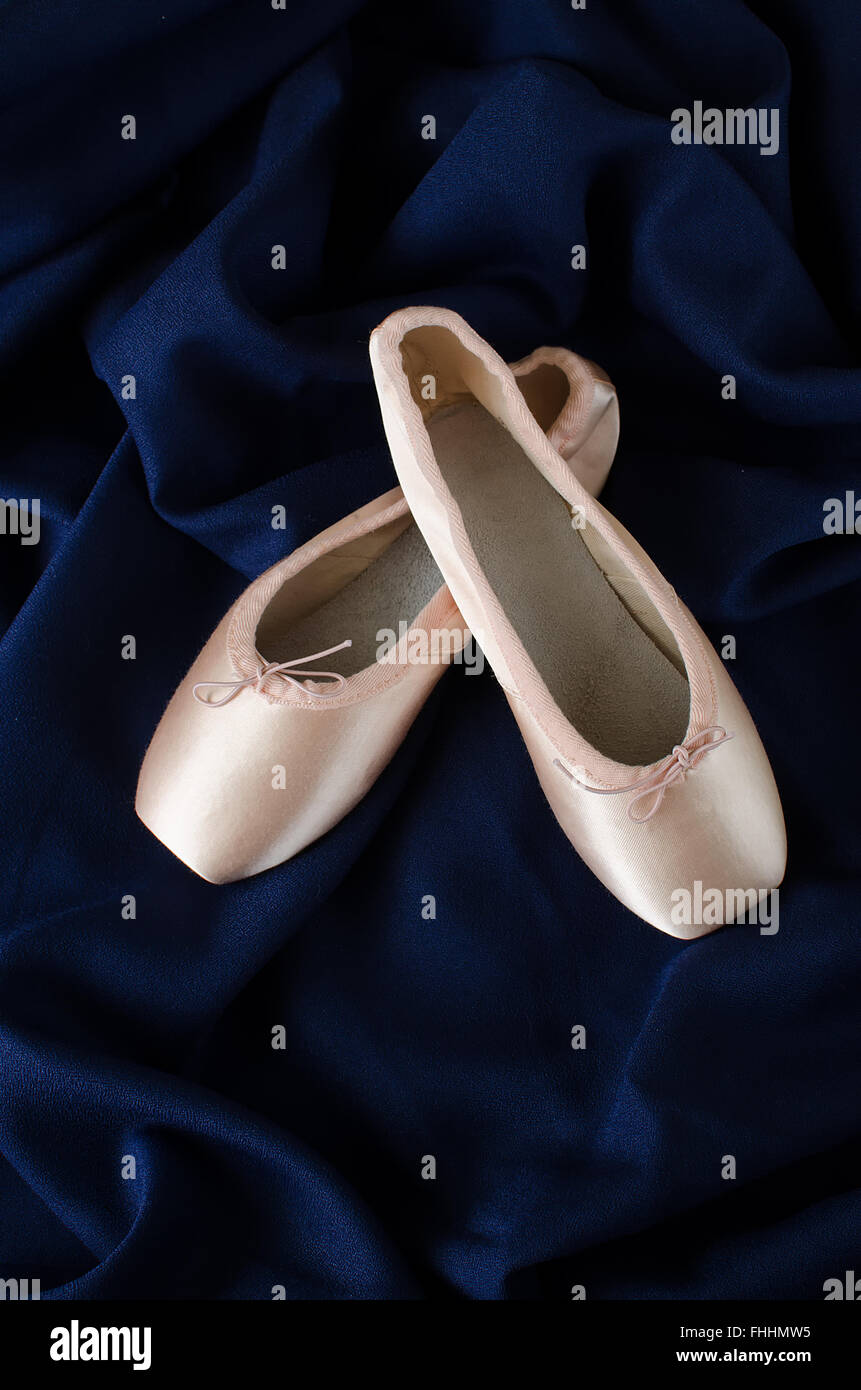 A pair of pointe shoes on blue background - Stock Image