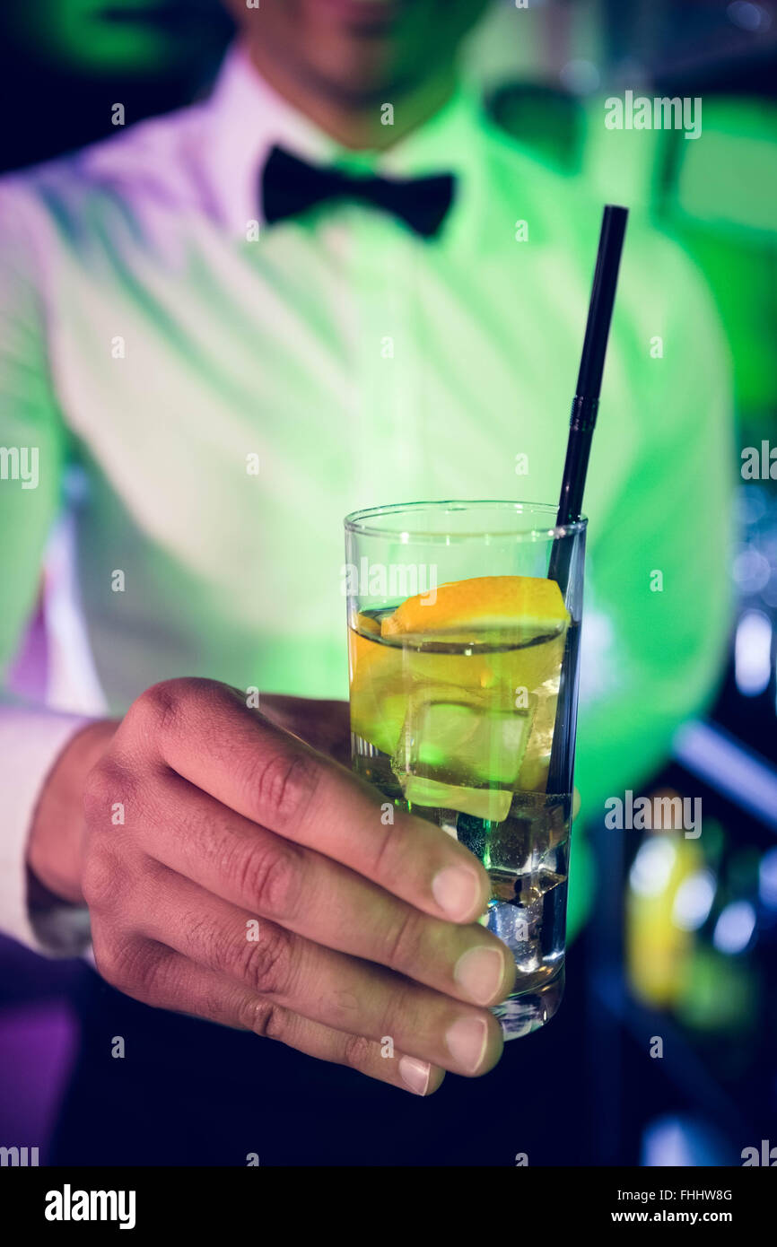 Bartender serving glass of gin - Stock Image