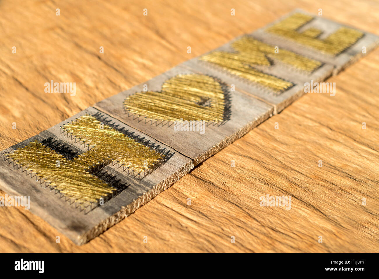 Home sweet home sign made of handmade wooden boards and golden string - Stock Image