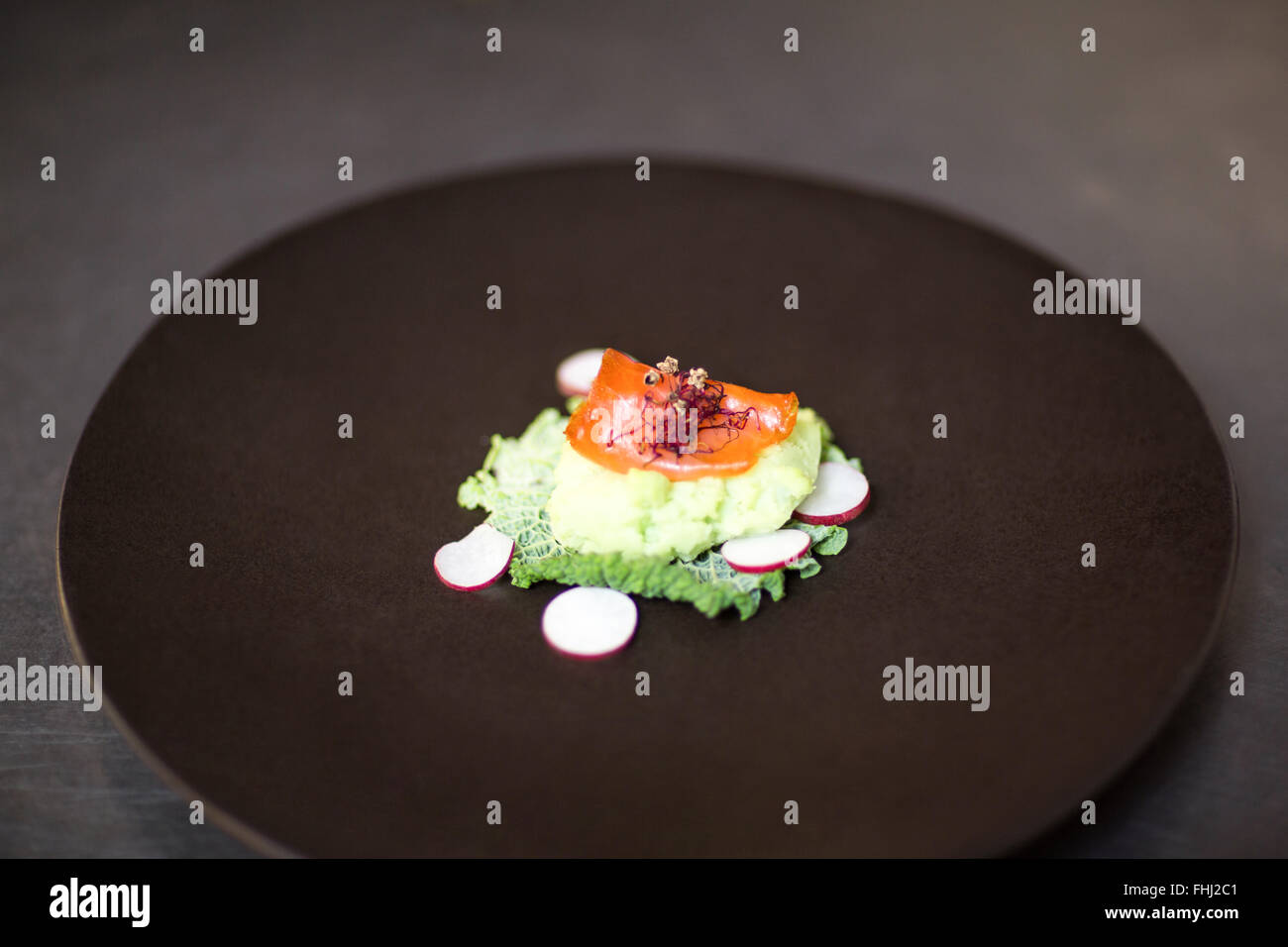 Salmon dinner on a plate on order station - Stock Image