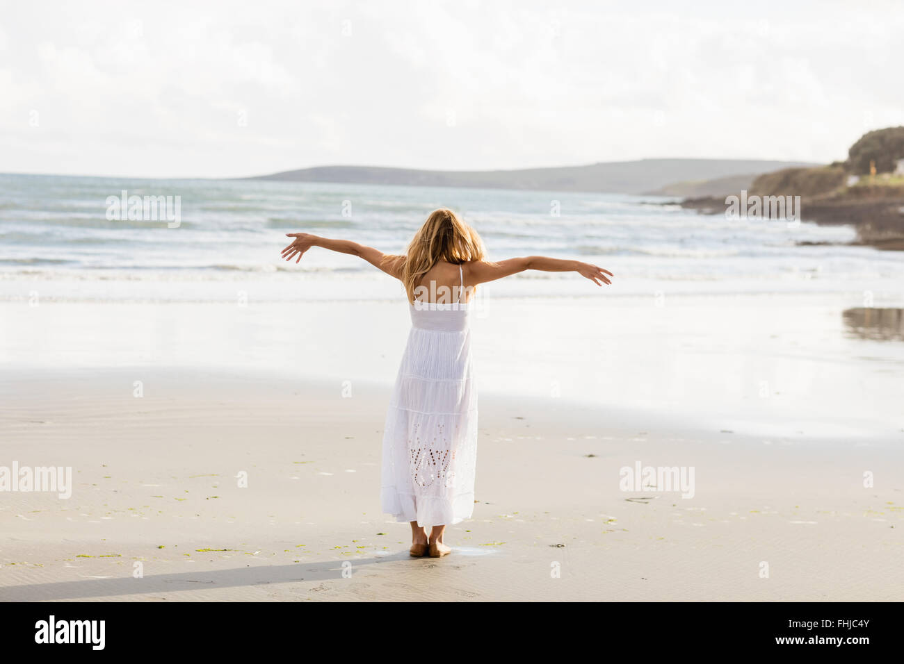Beautiful blonde woman with arms outstretched - Stock Image