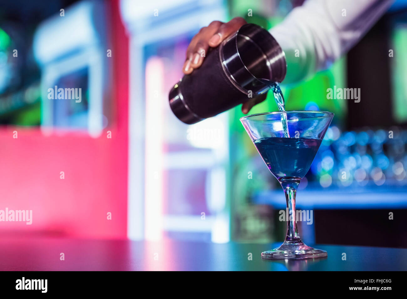 Bartender pouring cocktail from shaker - Stock Image