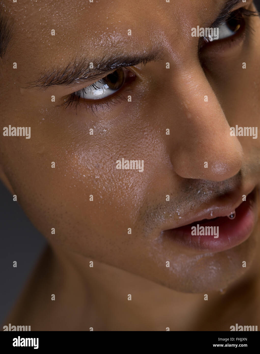 Close up of intense looking man with moisture on his face - Stock Image