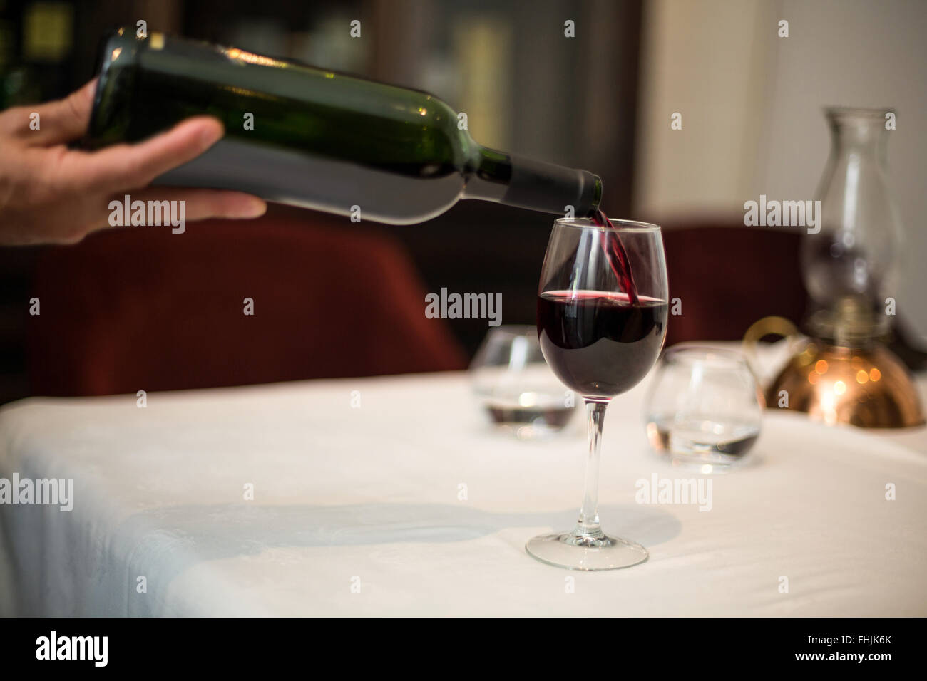 Waiter pouring a glass of red wine - Stock Image