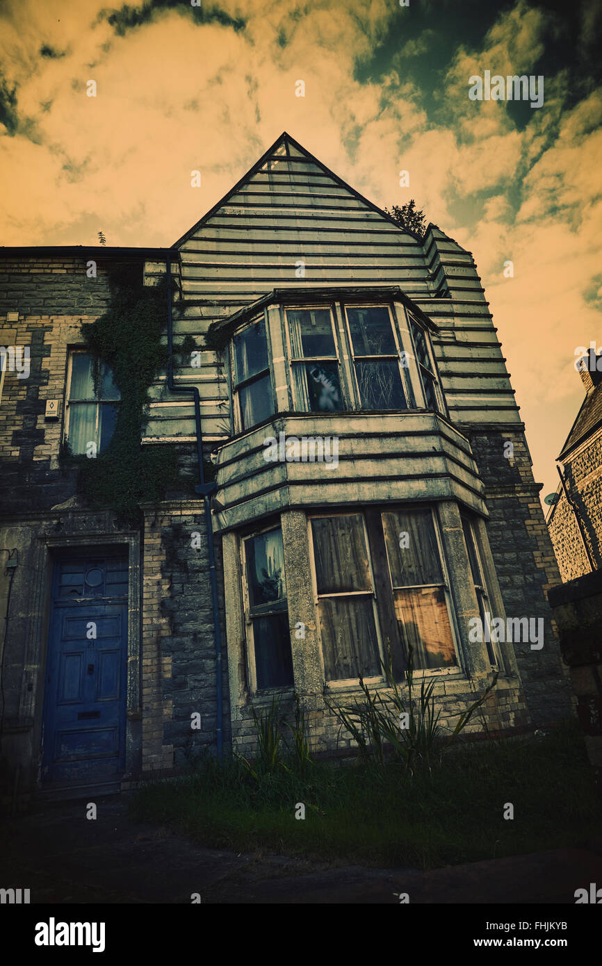 A Derelict run down urban house with a ghostly figure in upstairs window. Stock Photo
