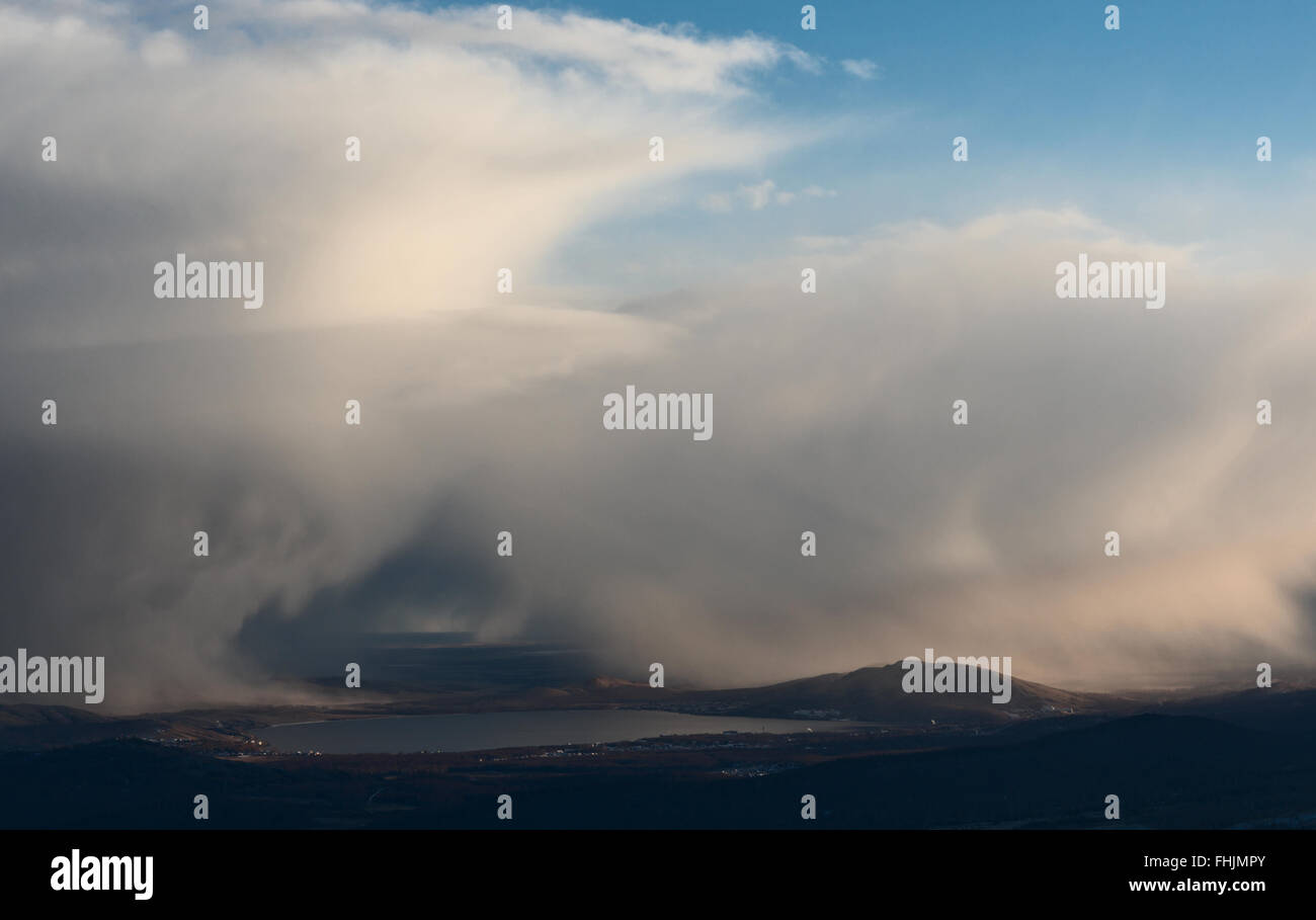 Snowstorm over lake and hills - Stock Image