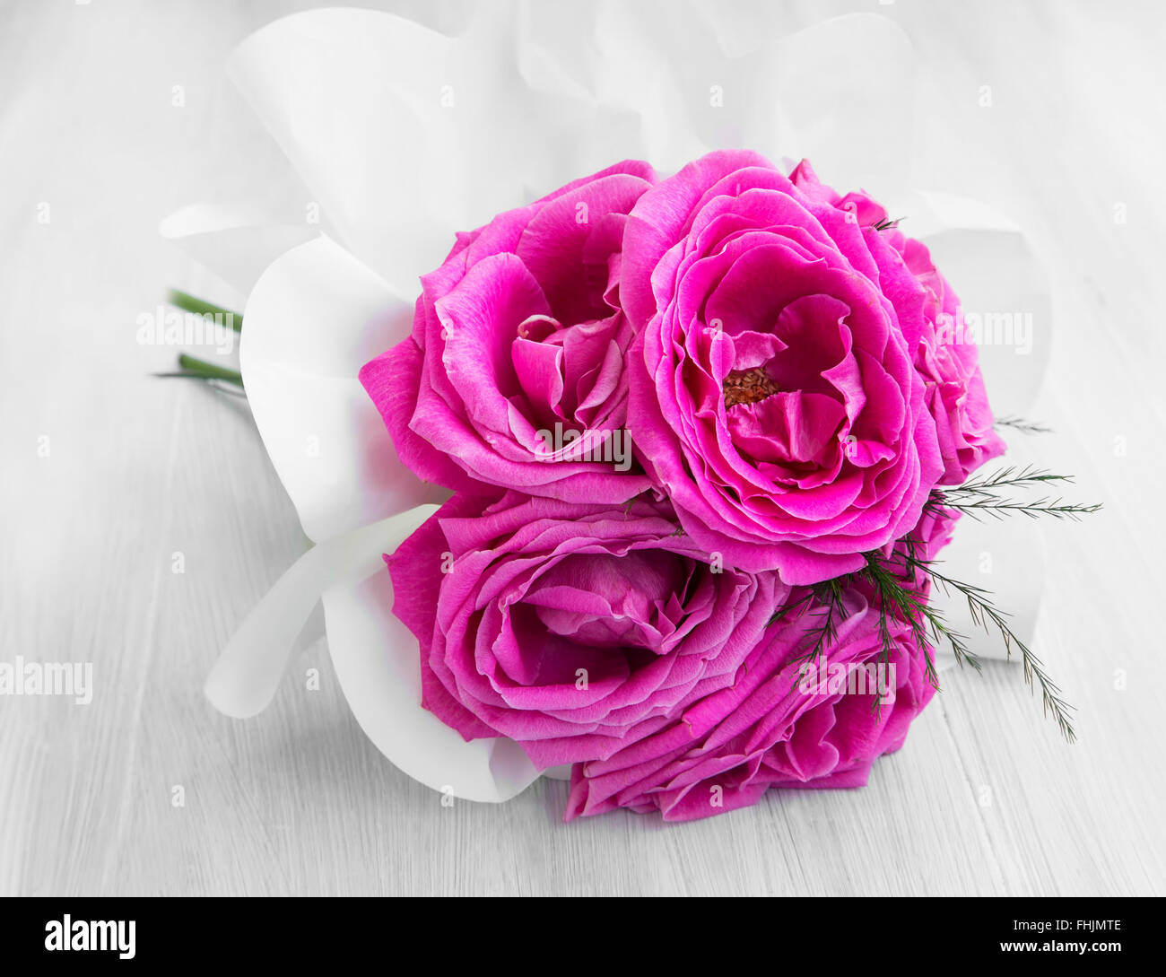 Delicate spring bouquet of pink roses on white painted wood - Stock Image