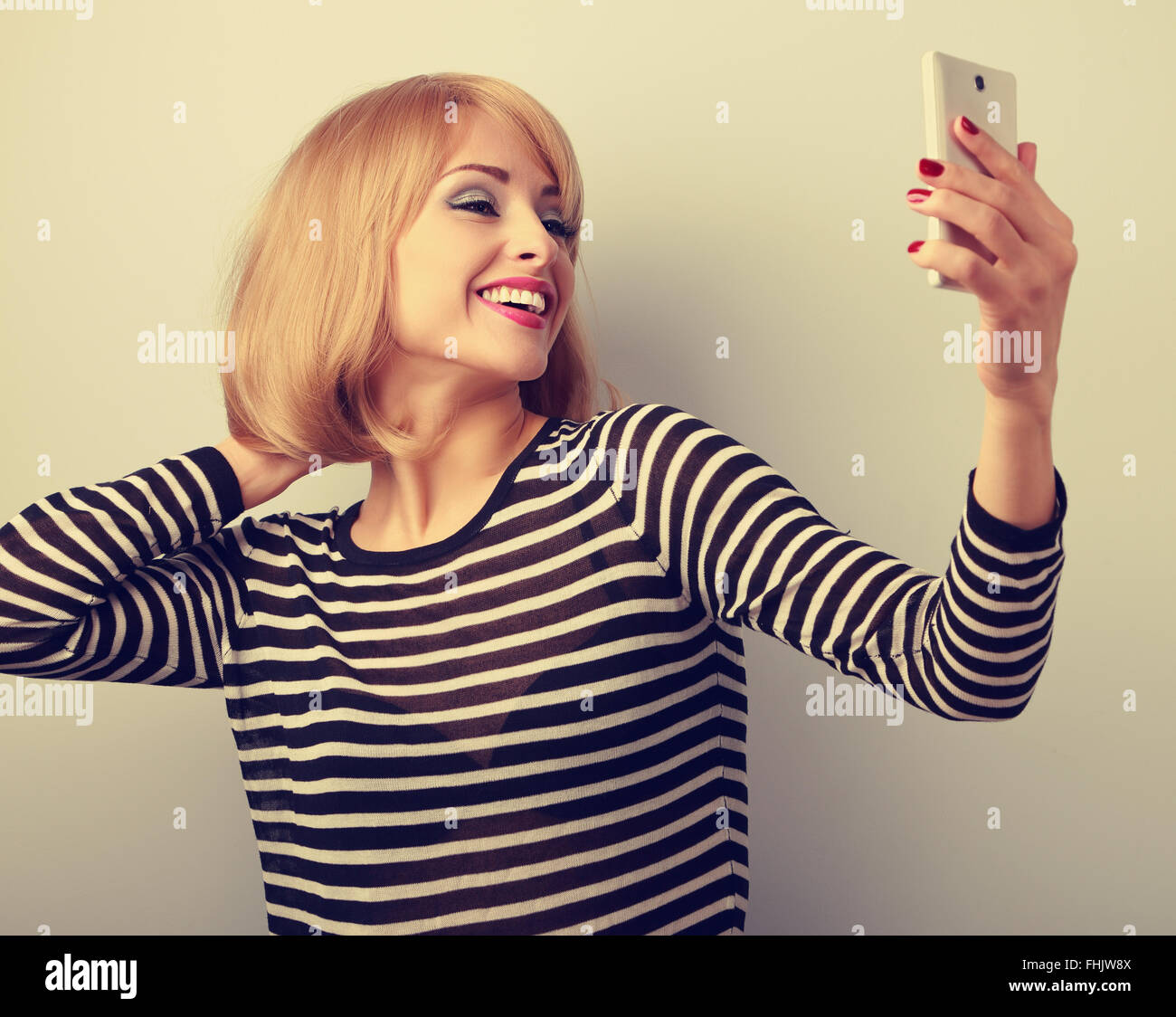 Funny cute blond woman making self photo of herself haircut and make-up on mobile phone. Toned closeup portrait Stock Photo