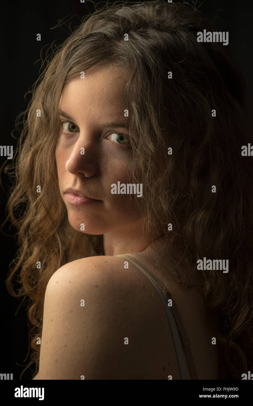 Unretouched photo of fair-skinned woman with wavy/curly brown hair, blue eyes and serious expression in dramatic - Stock Image