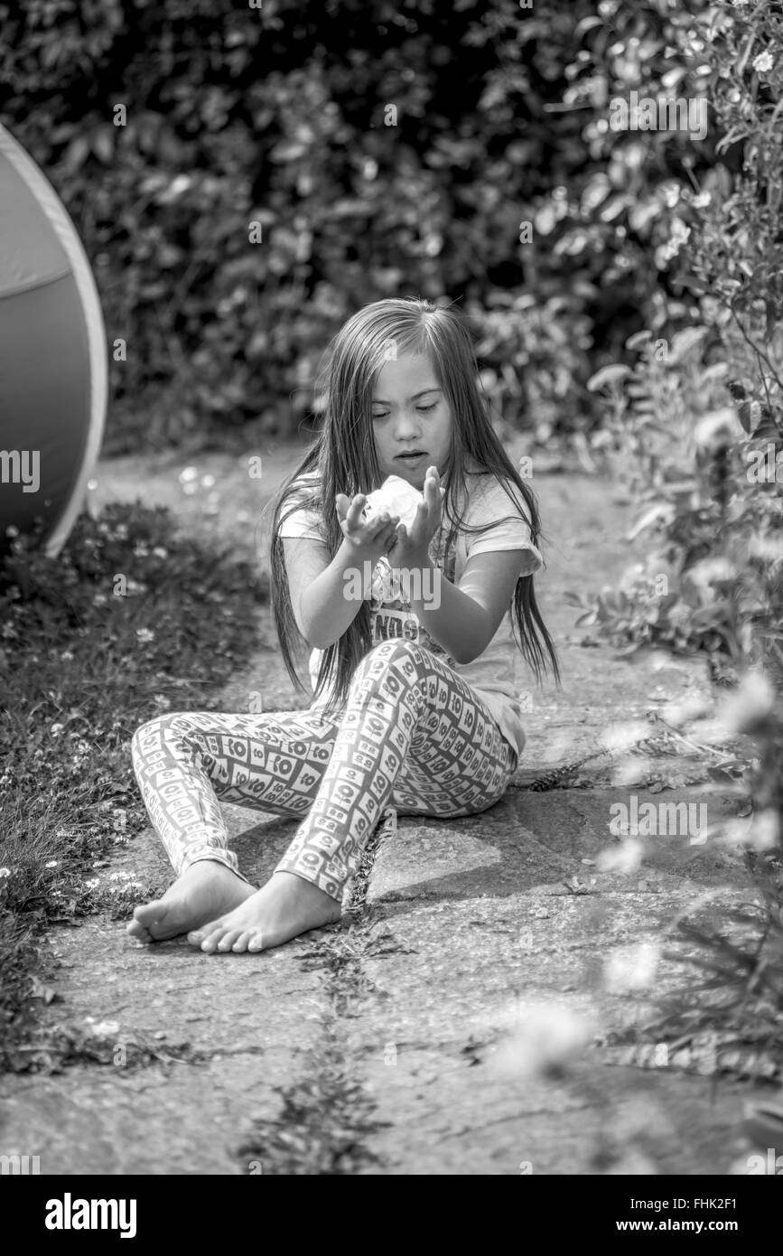 Downs Syndrome girl looking at a flower in the garden - Stock Image