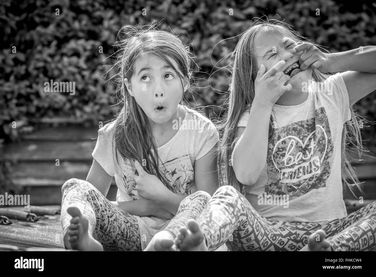 Downs Syndrome girl making funny faces with sister - Stock Image