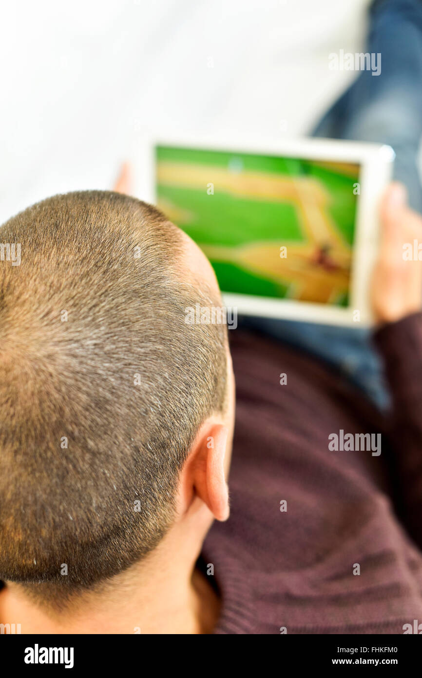 a young man lying on the couch watches a baseball game in streaming in his tablet computer - Stock Image