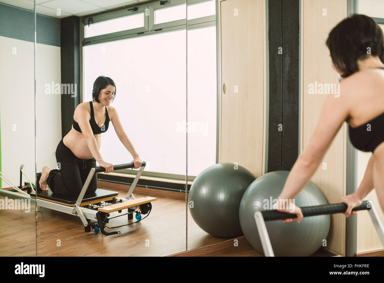 Pregnant woman doing Pilates exercises in a gym - Stock Image