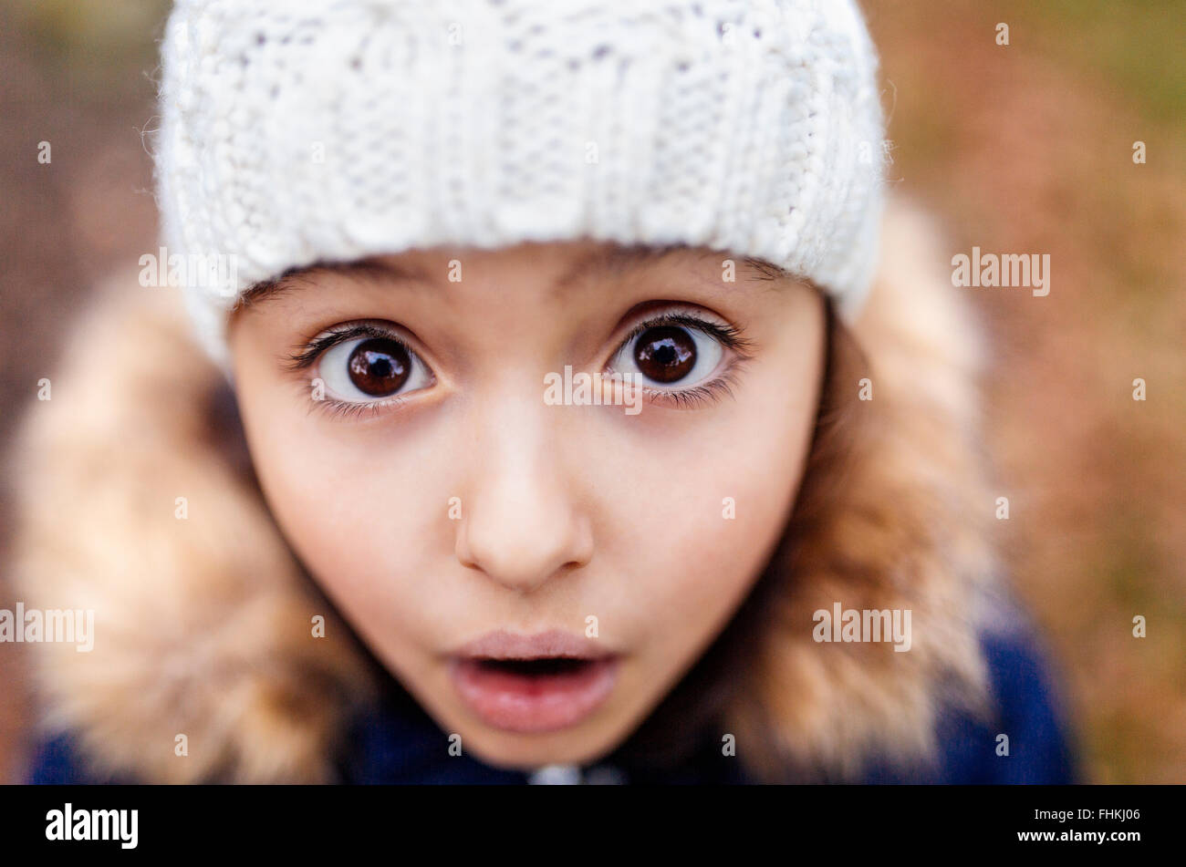 Portrait of little girl with eyes wide open - Stock Image