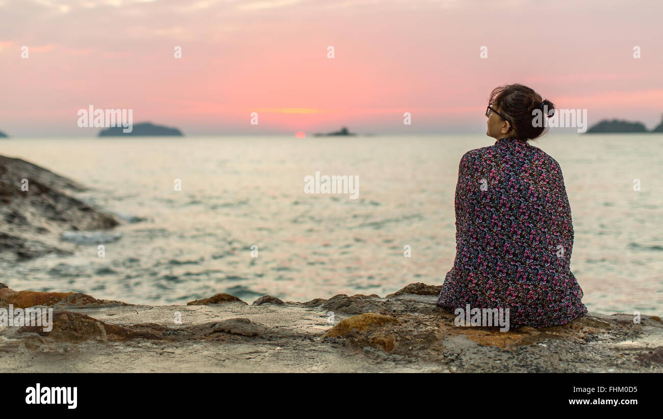 Woman wrapped in plaid sits lonely on the coast. - Stock Image