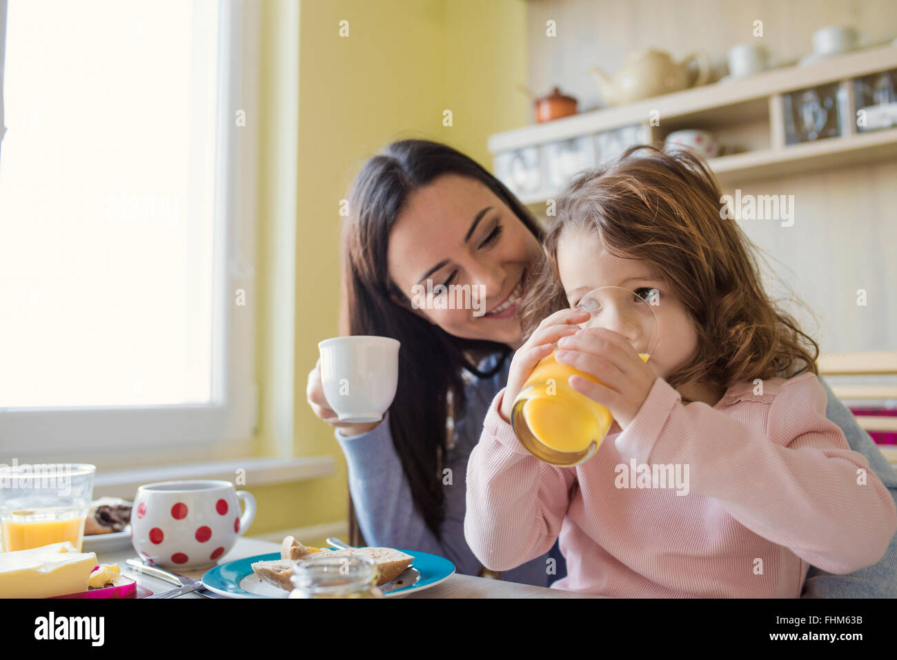 Mother and her little daughter together at breakfast table - Stock Image
