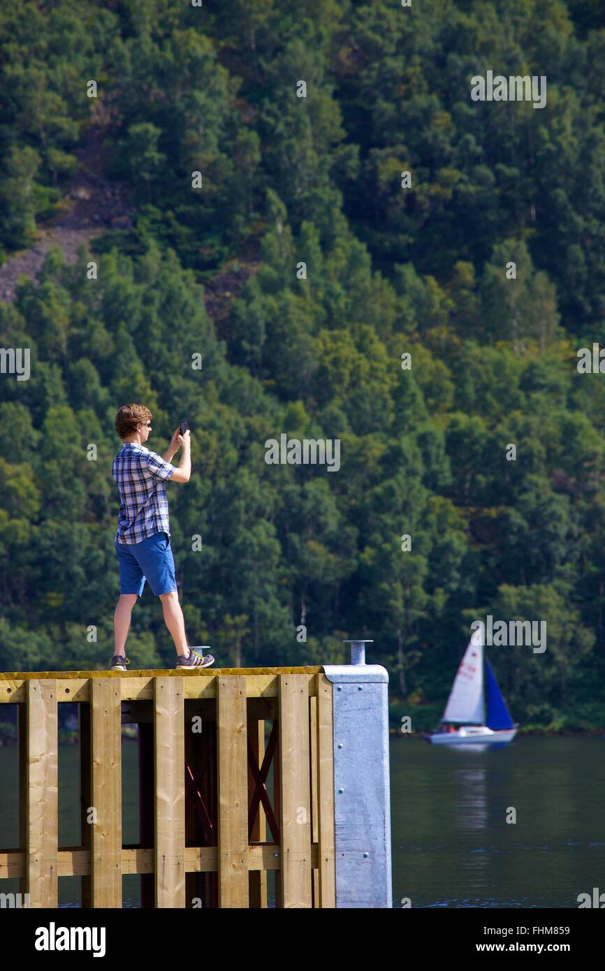 Lake District National Park. Man taking photograph with smart phone from a jetty on lake Ullswater. - Stock Image