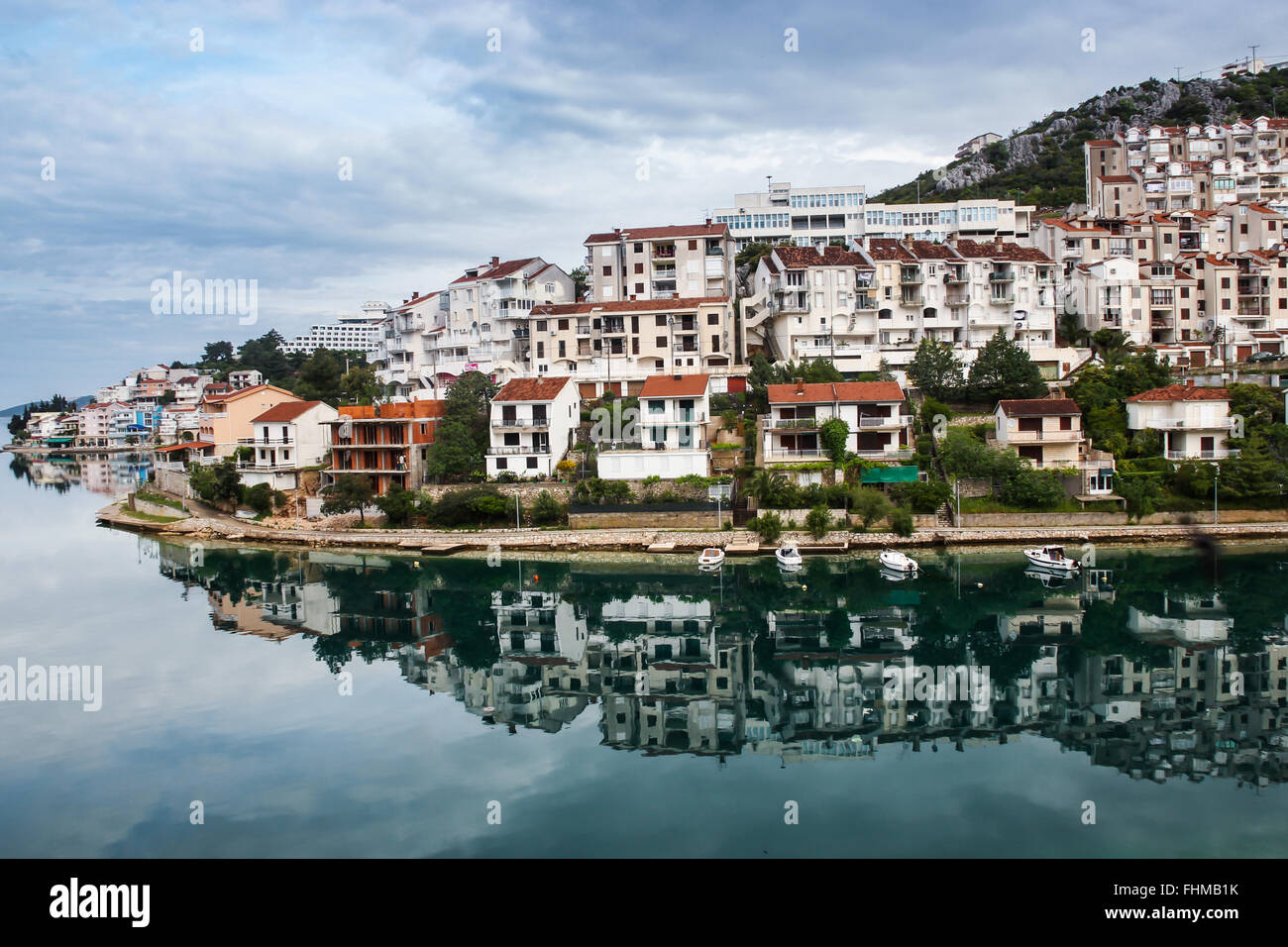 The nice reflection of a small village in Bosnia Herzegovina in the silent morning bay. The village was still sleeping. - Stock Image