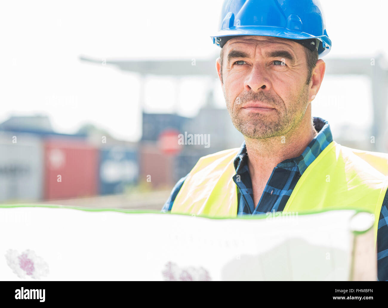 Man wearing hard hat holding document at container port - Stock Image