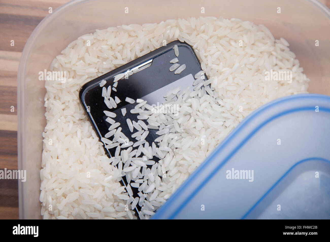 Using uncooked rice to draw out moisture from a mobile phone. - Stock Image