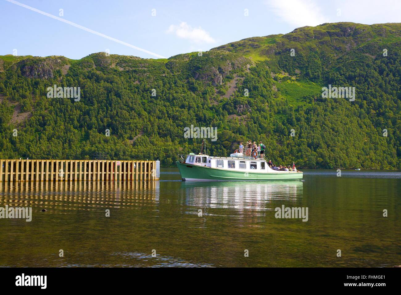 Lake District National Park. Tourists on a launch approaching a jetty on lake Ullswater. - Stock Image