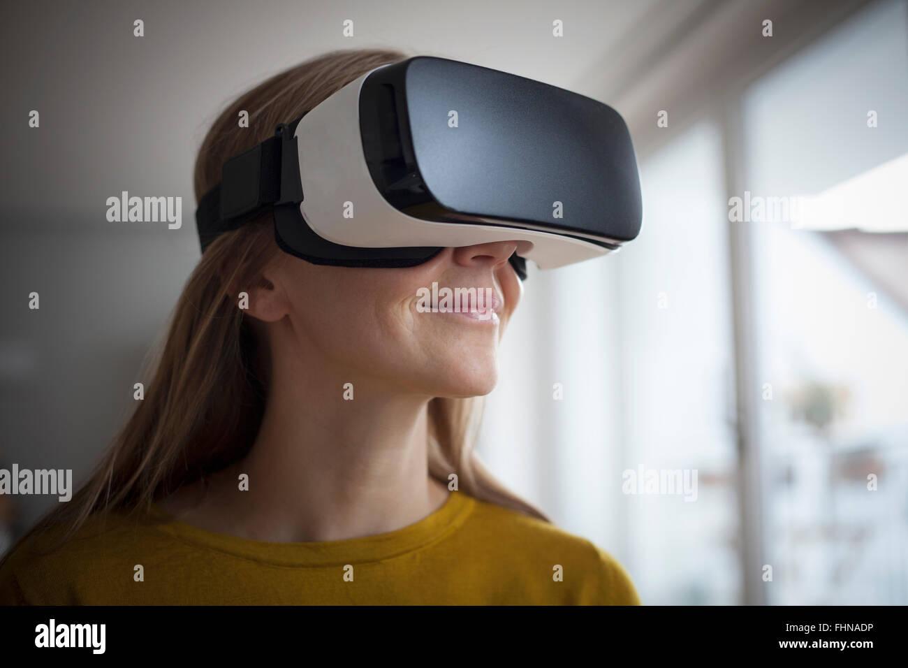 Smiling woman wearing Virtual Reality Glasses - Stock Image