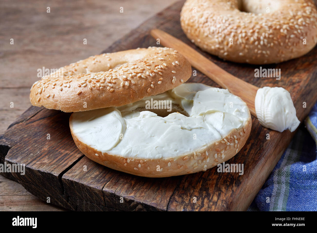 Bagel with cream cheese on wooden table - Stock Image