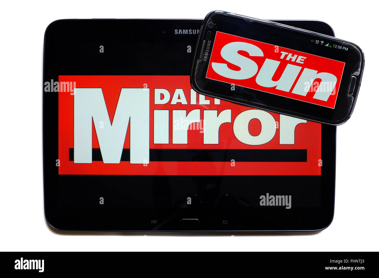 The logos of the Daily Mirror and The Sun newspapers displayed on the screens of a tablet and a smartphone. Stock Photo