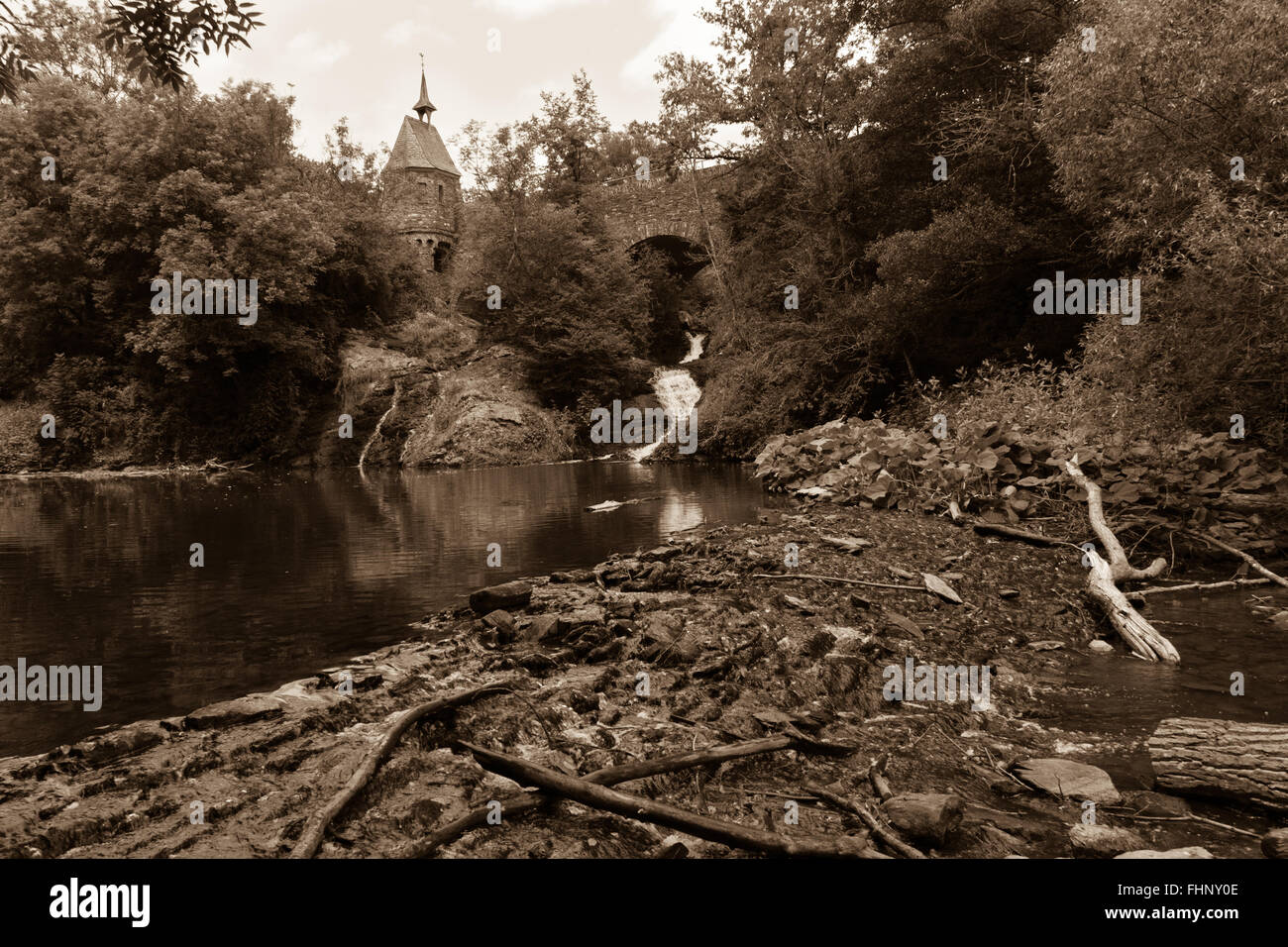 Old bridge, waterfall and tree branches in the foreground-Elzbach water stream near Eltz Castle, Germany - Stock Image