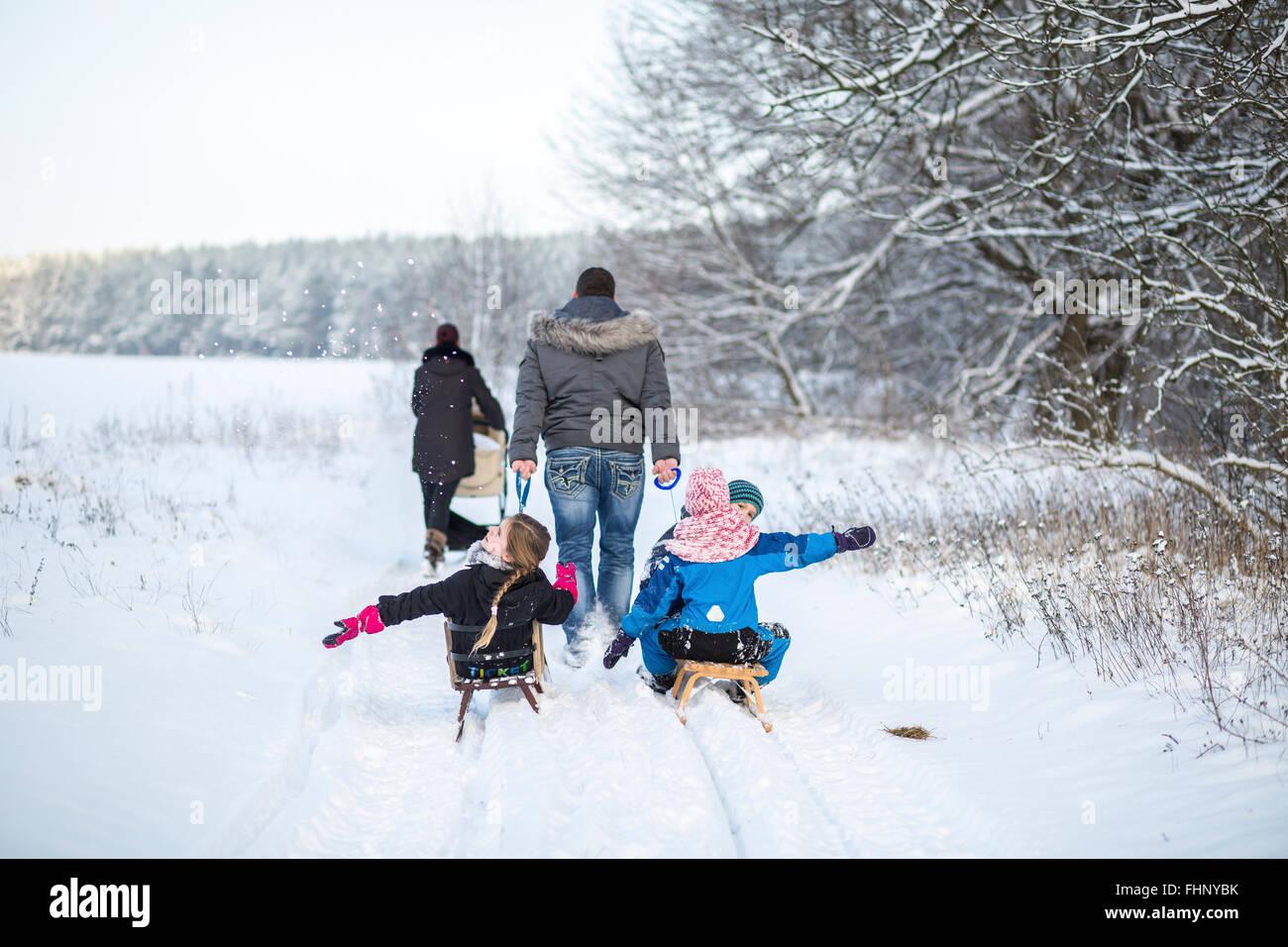 Germany, Brandenburg, back view of familiy with three children tobogganing - Stock Image