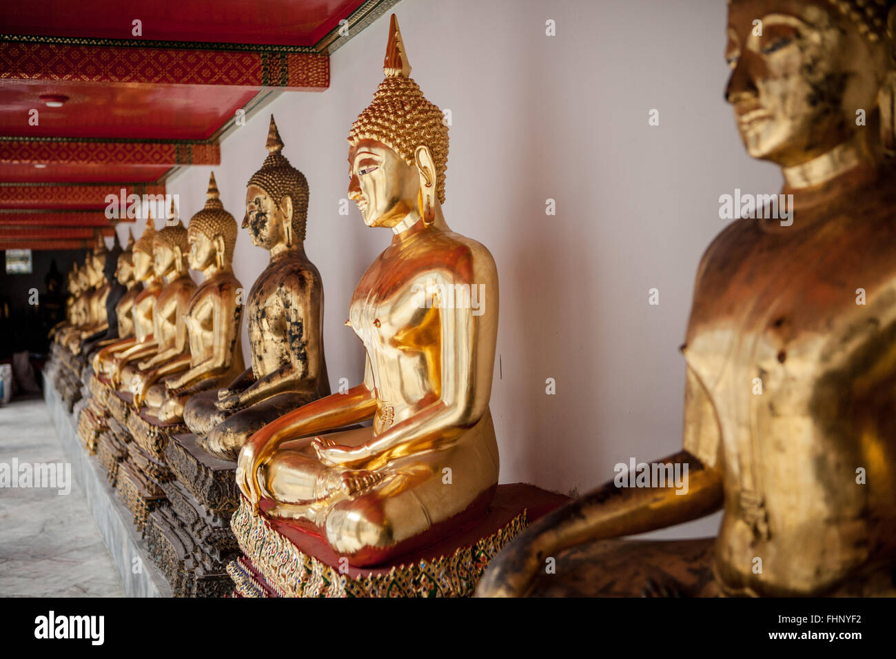 A row of seated, golden buddha statues at Wat Pho, a famous temple in Bangkok, Thailand - Stock Image
