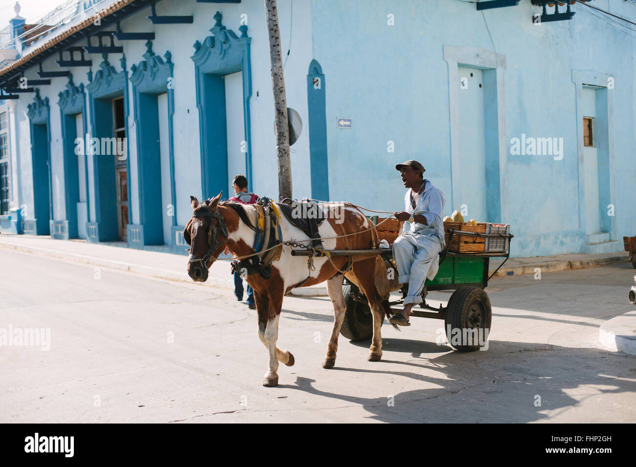 A man with his horse and cart driving through the streets of Trinidad and selling local produce. He man calls out - Stock Image