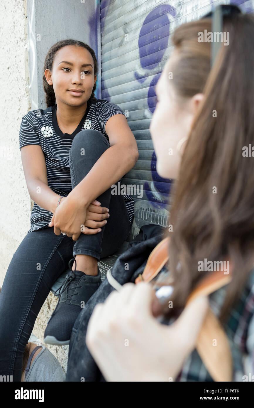 Teenage girls hanging around at roller shutter - Stock Image