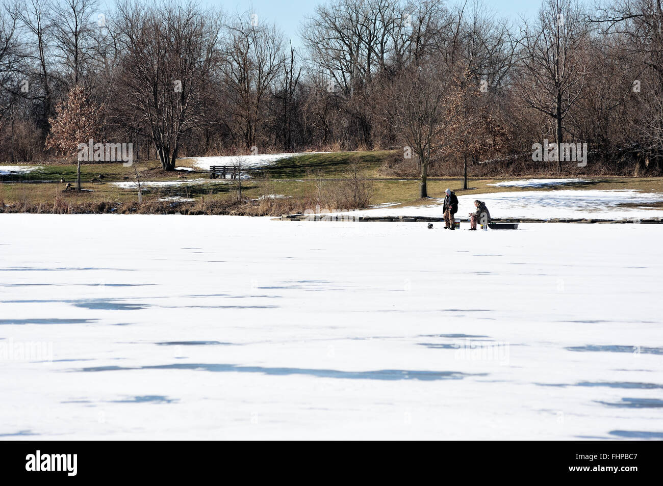 Pair of ice fishermen isolated near shore on a frozen lake in a forest preserve in Wayne, Illinois, USA. - Stock Image